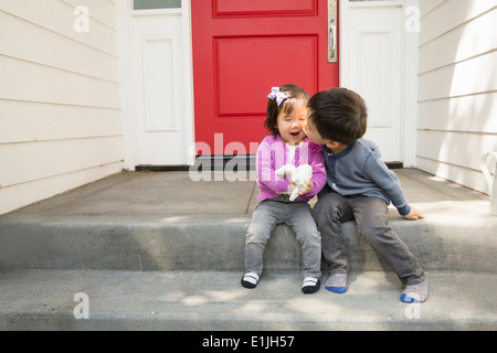 Brother kissing toddler sister on cheek - Stock Photo