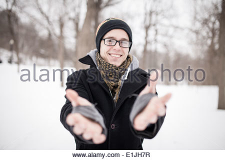 Young man standing in park reaching towards camera - Stock Photo