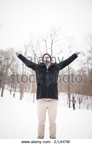 Young man standing in park with arms raised - Stock Photo