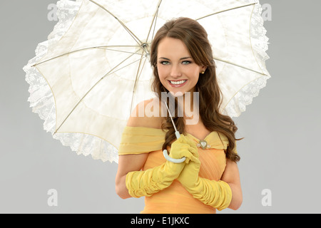 Young woman in Victorian dress holding umbrella isolated over neutral background - Stock Photo
