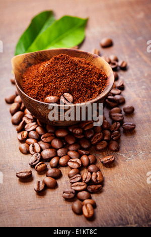 Wooden Bowl with ground coffee on wooden table - Stock Photo