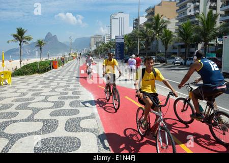 RIO DE JANEIRO, BRAZIL - APRIL 1, 2014: Cyclists ride along boardwalk bike path on Avenida Vieira Souto in Ipanema. - Stock Photo