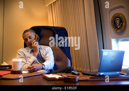 US President Barack Obama talks on the phone in his office aboard Air Force One April 10, 2014 on a flight back - Stock Photo