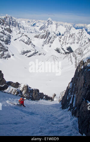 A male backcountry skier on tele skis descends a steep couloir with a unique limestone arch in it. Mt. French Peter - Stock Photo