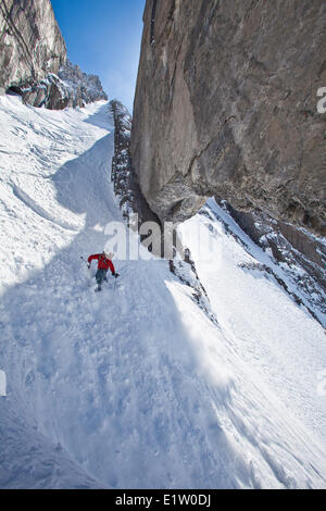 A male backcountry skier on tele skis drops into a steep couloir with a unique limestone arch in it. Mt. French - Stock Photo