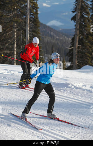 Male and female Cross Country Skiing at Sovereign Lake Nordic Centre, near Vernon, Okanagan, British Columbia, Canada - Stock Photo