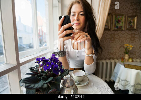 Young woman using smart phone at cafe table - Stock Photo