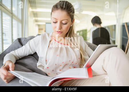 Young businesswoman with digital tablet reading book in office - Stock Photo