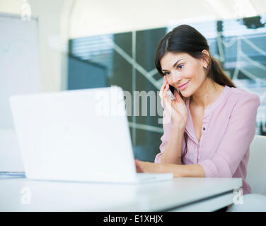 Beautiful young businesswoman using mobile phone while looking at laptop in office - Stock Photo
