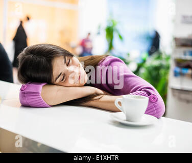 Young businesswoman sleeping at desk in office - Stock Photo