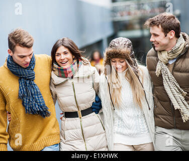 Happy young friends walking together outdoors - Stock Photo