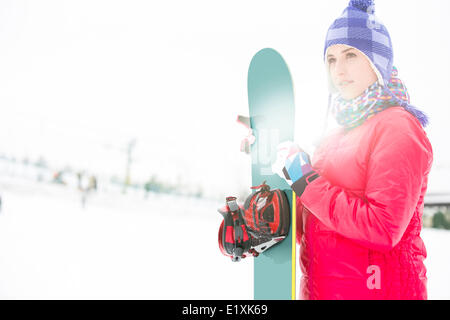Beautiful young woman in warm clothing holding snowboard during winter - Stock Photo