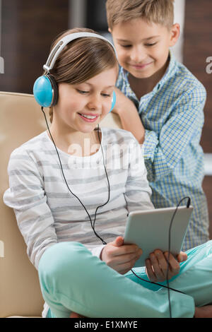 Cute girl listening music on digital tablet while brother standing behind her at home - Stock Photo