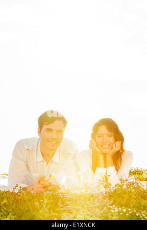 Portrait of young couple lying on grass against clear sky - Stock Photo