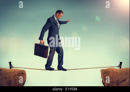 businessman predicament balancing or walking a tightrope or highwire. business concept of challenge, risk, danger, - Stock Photo