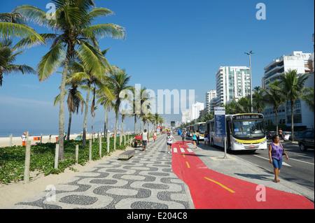 RIO DE JANEIRO, BRAZIL - APRIL 1, 2014: A local bus stops along boardwalk bike path on Avenida Vieira Souto in Ipanema. - Stock Photo