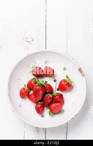 Strawberry in Vintage ceramic colander on white wooden background - Stock Photo