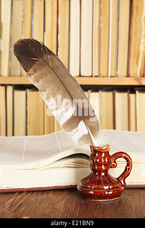 Vintage still-life. Quill in inkstand on a background of books - Stockfoto