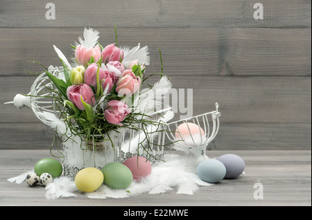 easter composition with eggs and pastel tulip flowers. nostalgic home interior. retro style colored picture - Stockfoto