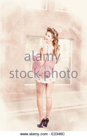 Cute vintage portrait of a retro pin up woman carrying striped shop bag when window shopping for hair and makeup - Stock Photo