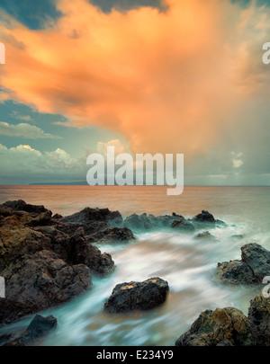 Sunrise and clouds on rocky beach. Maui, Hawaii - Stock Photo