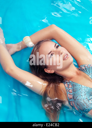 Portrait of a beautiful young woman with blond hair wearing a swimsuit lying in blue water - Stock Photo