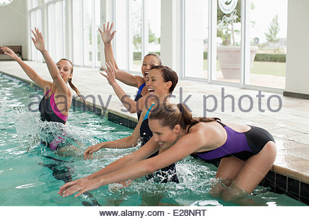 Enthusiastic women jumping in swimming pool - Stock Photo