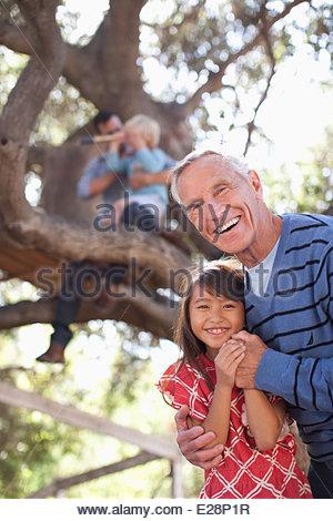 Older man hugging granddaughter outdoors - Stock Photo