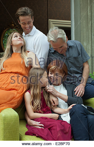 Portrait of smiling multi-generation family sitting on sofa - Stock Photo