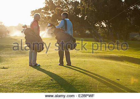 Men carrying golf bags on golf course - Stockfoto