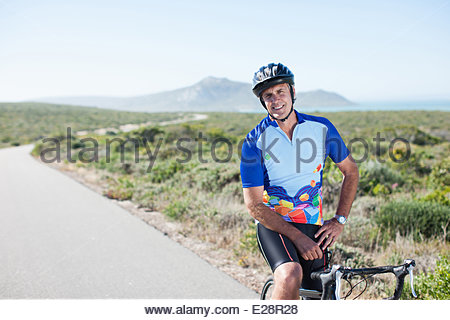 Man in helmet sitting on bicycle - Stock Photo