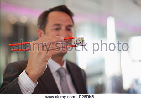 Businessman eating sushi - Stock Photo