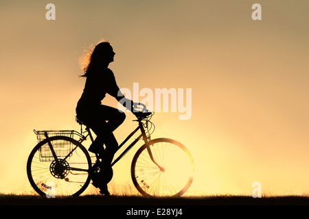 A silhouette of a happy woman outside riding a vintage bicycle, isolated in front of a sunset in the sky. Copyspace. - Stock Photo