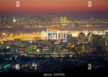 A rare view of the Oakland and San Francisco skylines at night along with the Bay Bridge - Stock Photo