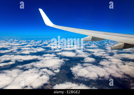 Clouds, sky and earth as seen through window of an aircraft - Stock Photo