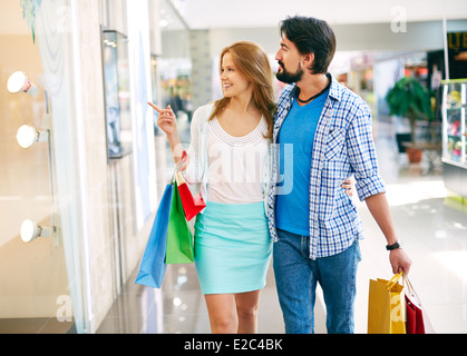 Portrait of young couple shopping in the mall - Stock Photo