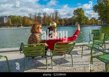 France Paris Les Tuileries Gardens tourist couple photographing themselves in background Golden Sphere artwork by - Stock Photo
