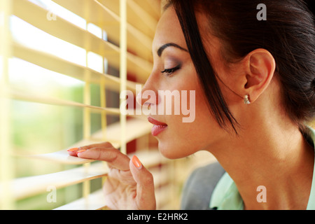 Beautiful businesswoman looking in window at office - Stock Photo