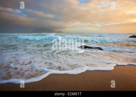 View from the beach at Bloubergstrand over the ocean with a classic view of Table Mountain across the bay. - Stock Photo