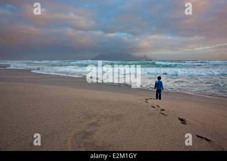 Young boy on the beach at Bloubergstrand looking out over the ocean with a classic view of Table Mountain across - Stock Photo