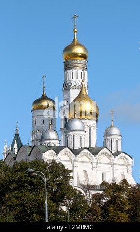 Lovely view from Moscow Ivan the Great bell tower and the church against the blue sky and trees - Stock Photo