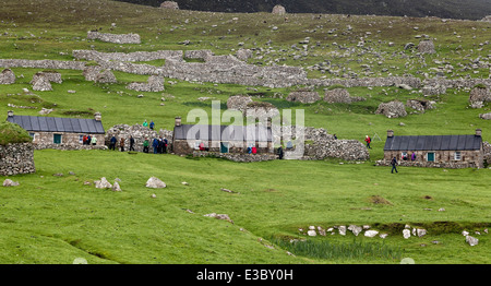 Tourists exploring the abandoned blackhouses on the main street in Village Bay, St. Kilda - Stock Photo