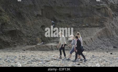 Four ladies take a morning walk on the beach - Stock Photo