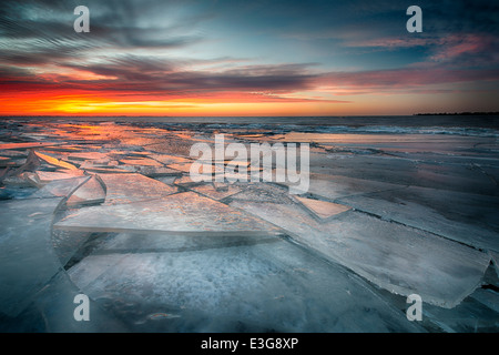 Ice sheets stack along the shores of Lake St. Clair in Southeast Michigan, reflecting the colors of twilight. - Stock Photo