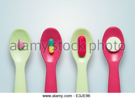 Four plastic spoons, each containing a different pill - Stock Photo