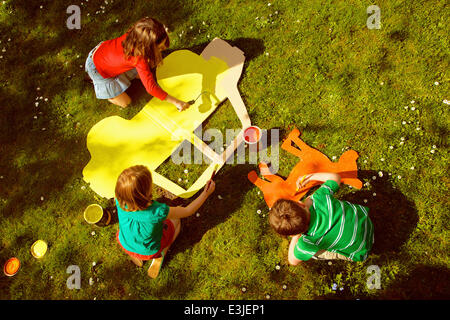 Children Painting Cardboard Cut Outs in Garden - Stock Photo