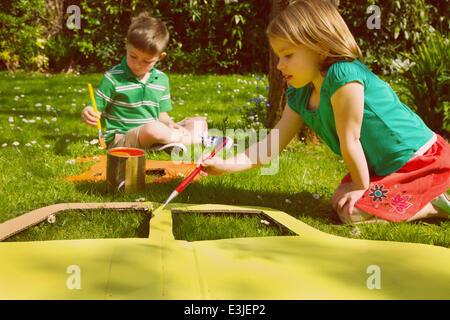Jungen und Mädchen malen Karton Cut Outs im Garten - Stockfoto