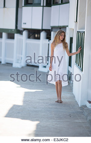 Teenage Girl Sliding Hand on Exterior Wall of Building - Stock Photo