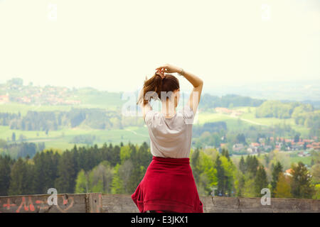 Back View of Young Woman Adjusting Hair Looking at Landscape - Stock Photo