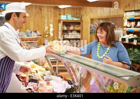 Male Sales Assistant Serving Customer In Delicatessen - Stock Photo